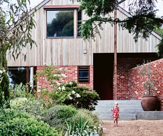 Reclaimed brick home facade with steeply pitched roof
