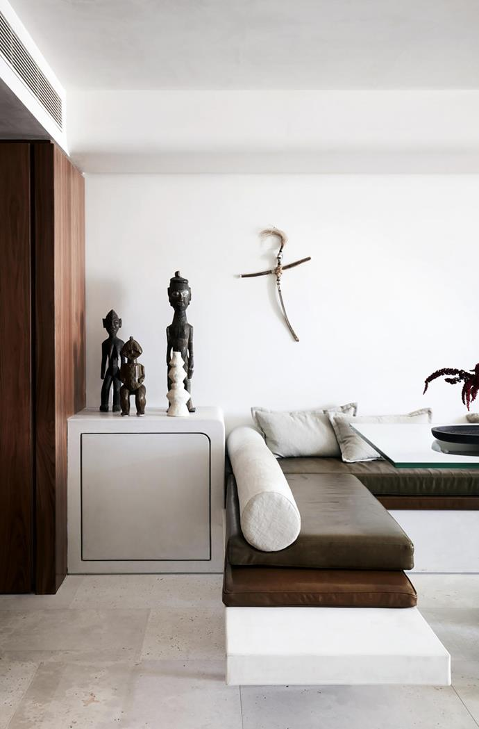 Custom banquette designed by Amber Road and made by Atelier furniture with totem by Emma Gale and client's own African statues. Marmorino wall finish by artisan Fernando.