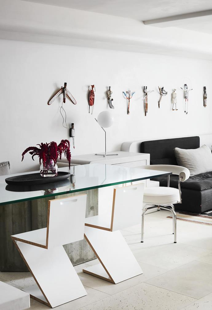 Cassina 'Zig Zag' chairs by Gerrit Rietveld and 'LC7' chair by Charlotte Perriand, all from Cult, surround a vintage Saporiti concrete and glass dining table from Vampt Vintage Design. Wall sculptures by Michelle Connolly.