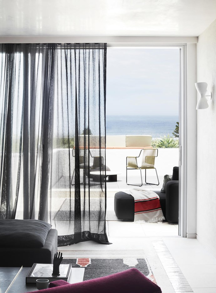 Curtains by Solis in 'Aero' from Unique Fabrics frame the terrace, that features a Paola Lenti 'Isole' coffee table, Roda 'Harp' outdoor chairs and 'Dandy' modular sofa. Sconce by Anna Charlesworth.