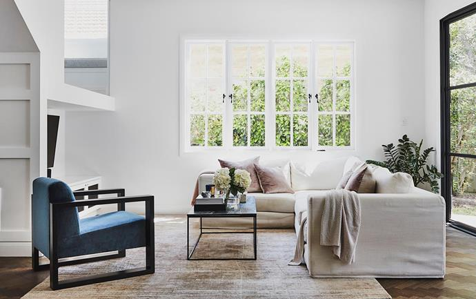"The windows are part of the design so I didn't want to cover them with curtains or blinds,"" says Julia. A glass window over the TV area reveals the staircase. Bifold metal doors, The Steel Door Company. Custom sofa, blue chair and coffee table, Flow Interiors & Styling. Cushions, Smithmade. Throw, Sheridan."