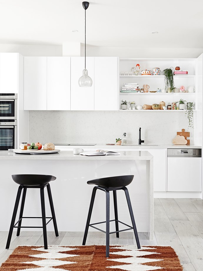**Minimalist** Trends come and go, but monochrome minimalism  is here to stay. The perennial white palette is clean, calming and bright, and when contrasted with the black tapware and bar stools, it feels oh-so modern. The seamless cabinets and open shelving allow you to stow some pieces away and display others front and centre. *Photo:* Eve Wilson