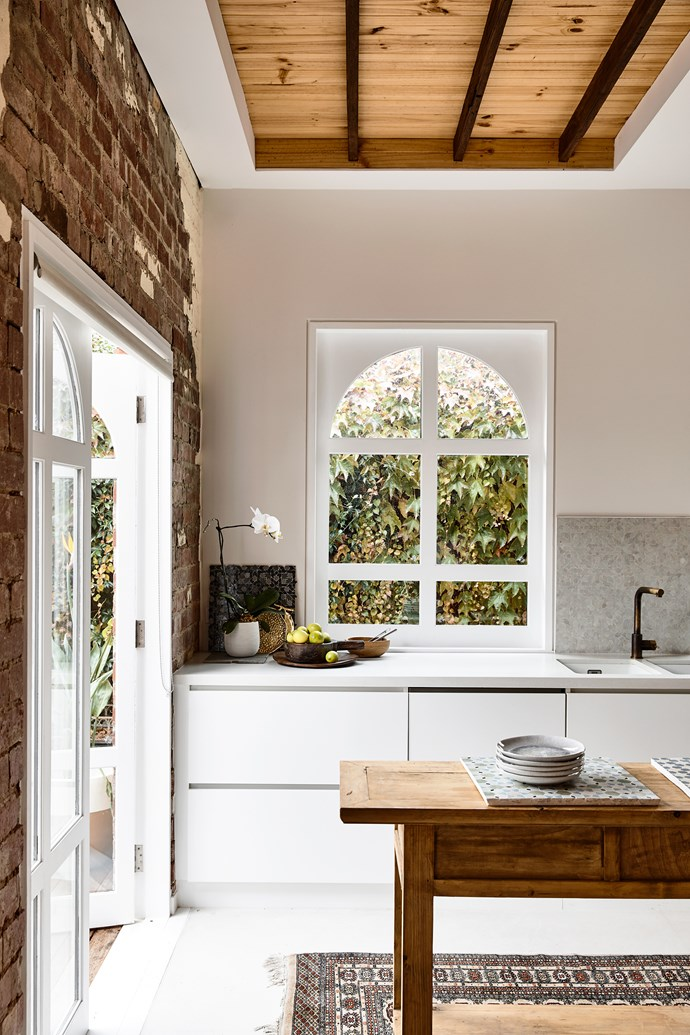 **Warehouse vibe** The original Art-Deco features of this home shine through in the kitchen, from the exposed beams to the textural brick wall. Meanwhile, an arch window provides the perfect backdrop for days spent baking and an antique rug tucked under the timber island keeps it cosy. *Photo:* Derek Swalwell