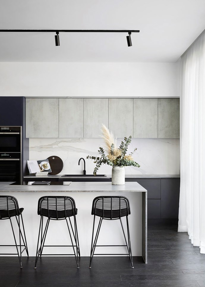"**Textural finishes** This contemporary space mixes materials to great effect. A [marble splashback](https://www.homestolove.com.au/statement-kitchen-splashbacks-4432|target=""_blank"") adds elegance to the industrial grey concrete, and delicate porcelain finishes are grounded by the timber flooring. From the sink to the stools, the neutral colour palette proves sophistication need not be subtle. *Photo:* Tess Kelly"
