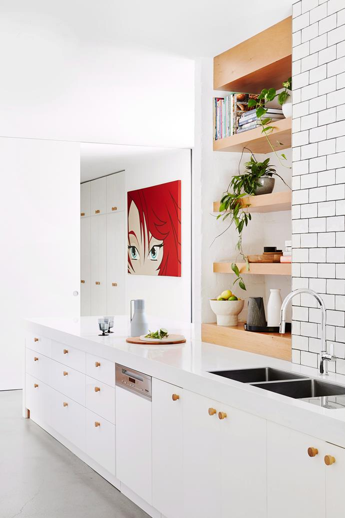"**All-white** You can't go wrong with an [all-white kitchen](https://www.homestolove.com.au/all-white-kitchen-design-6370|target=""_blank""). Slim, awkward spaces are made functional with custom shelving. The woodgrain is repeated on the door handles to cut through the white surfaces. *Photo:* Annette O'Brien"