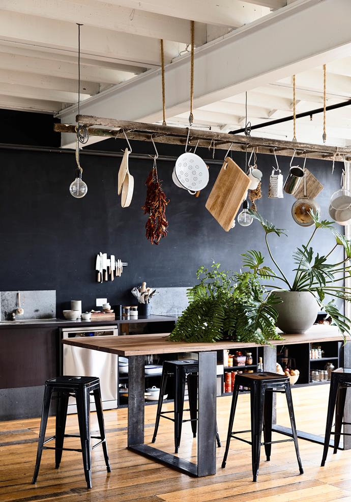 **Industrial revolution** There's more to sky-high ceilings than just good looks! Suspended from the rafters, this ladder creates a lofty storage solution for boards, pots and pans. When you're not entertaining, the spare dining space can be utilised to display indoor plants. *Photo* Nick McDonald
