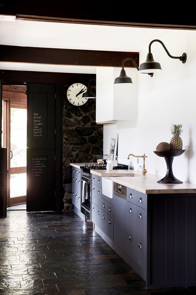 """**Modern Provincial** For those with a penchant for [French provincial design](https://www.homestolove.com.au/french-provincial-kitchens-6332 target=""""_blank""""), this contemporary kitchen is a study in how to combine the best of both. Curved ornate fittings, such as the wall lamps and decorative brass sink mixer, add charm to the cabinets' clean, minimalist lines. A pantry door becomes a clever calendar or grocery list with a coat of chalkboard paint. *Photo:* Chris Warnes"""