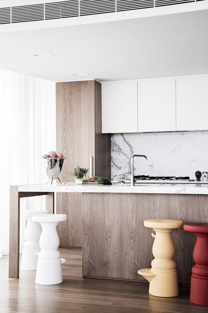 **Soft luxe** A marble splashback and sparkling chrome tapware add a luxe touch to this warm and inviting space. Semi-sheer curtains diffuse the light and create a more cosy kitchen space. Their gentle, draped lines balance the sharp right angles of the island, cabinets and benches. *Photo:* Maree Homer
