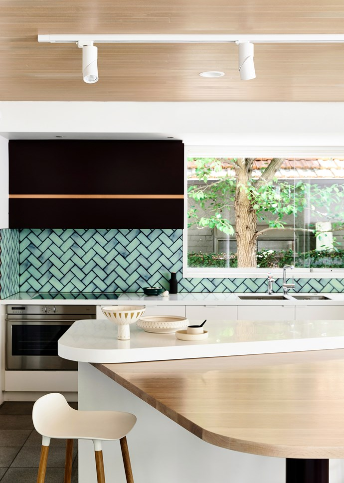 "**Splash of colour** Think of your kitchen splashback as the perfect place to introduce colour and pattern. Take these aquamarine tiles, which transform the room from understated to elevated. The layered two-tone curves of the [kitchen island](https://www.homestolove.com.au/8-kitchen-islands-to-inspire-your-next-kitchen-renovation-5686|target=""_blank"") also visually separate the food prep bench space from the dining area, masterfully fusing form with function."