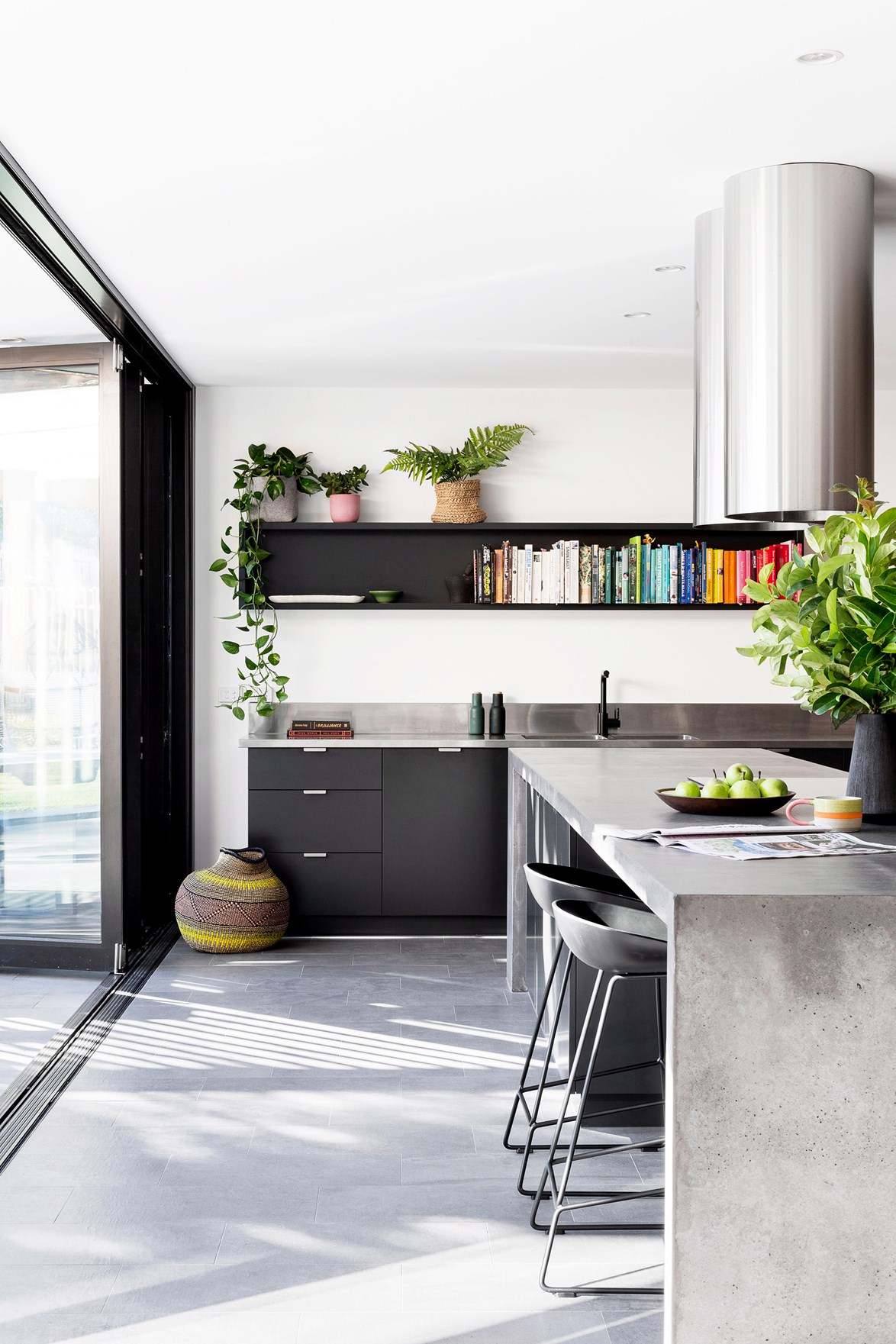 <p>**INSTALL A WALL-MOUNTED SHELVING UNIT**<p> <P>This industrial kitchen forgoes a full-length splashback for a striking wall-mounted shelving unit. A series of colour-coordinated books show that this is a truly multi-functional family hub where the kids complete their homework as meals are prepared.<p> <p>*Photo: Martina Gemmola / bauersyndication.com.au*<P>