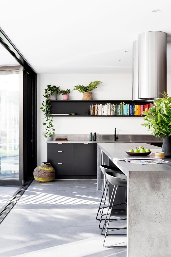 **Concrete chic** Concrete in the kitchen? Don't mind if we do! Concrete is a practical, durable alternative to laminate and granite because it resists scratches and chips and can be moulded into custom shapes. Here, a seamless concrete island doubles as a dining table, while the wall-mounted shelving unit above the sink makes good use of the available space, and keeps your cookbook collection right where you need it. *Photo:* Martina Gemmola