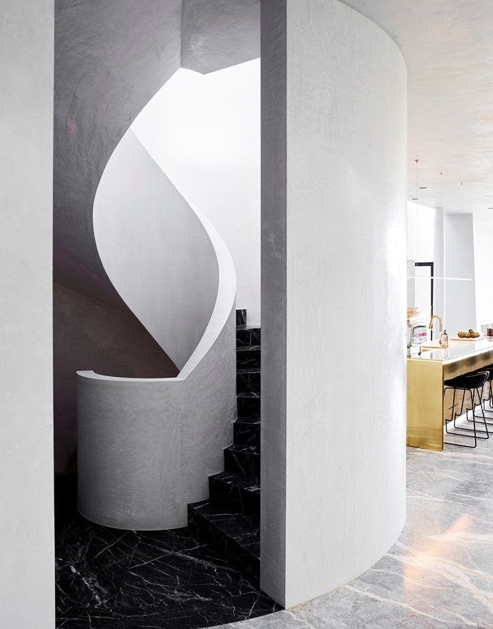 Light pours down the black marble spiral staircase from a domed skylight in this Sydney home by Rob Mills Architecture & Interiors. The kitchen features a polished brass island and Moros 'Fjord' bar stools from Hub. *Photograph*: Mark Roper. From *Belle* December/January 2017/18.