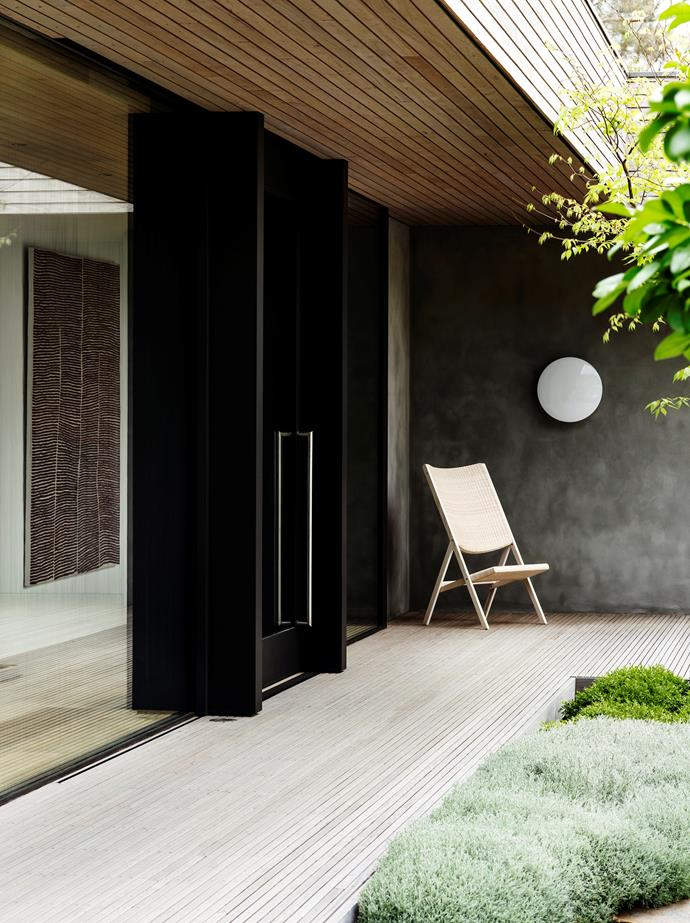 This Mornington Peninsula home designed by Reno Rizzo of Inarc Architects features a restrained palette of materials to create a clean, spare and deliberate mood. The front entrance features a Molteni&C 'D.270.2' chair by Giò Ponti for Hub. Louis Poulsen 'AJ Discus' light. Blackbutt decking. *Photograph*: Nicholas Watt. From *Belle* August/September 2016.