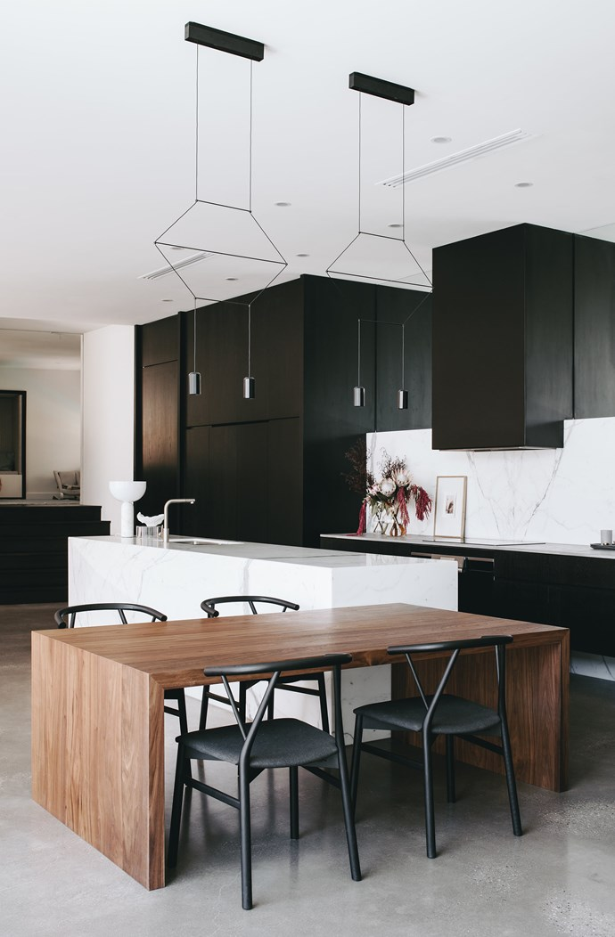 Concealed appliances and integrated doors into the butler's pantry and laundry meld into the surrounding joinery and create a calm and ordered appearance in this kitchen designed by Williams Burton Leopardi.  The black Vibia 'Wireflow Lineal' lights are from Koda Lighting. *Photograph*: Christopher Morrison. From *Belle* April 2018.