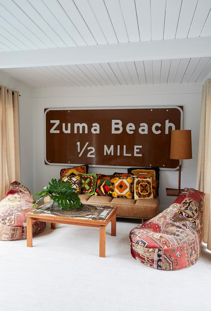A pair of plump Turkish beanbags, colourful woollen cushions and leather daybed make the guest house warm and inviting. The oversized Zuma Beach sign is a beloved find.