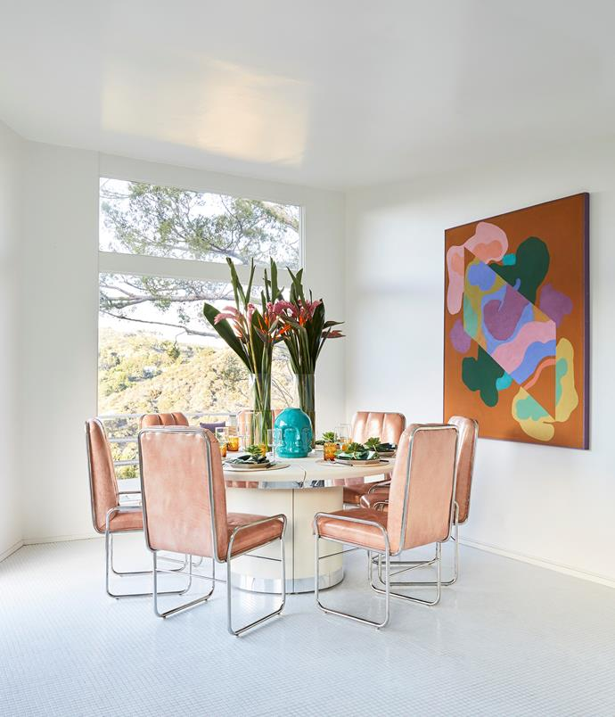 Vintage buys in bright colours pop against the dining room's white walls and floor. The table, chairs and artwork were all bought from the same store in Miami.