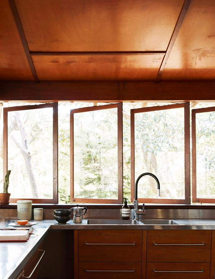 Pivot windows allow natural light and fresh air to flood this timber kitchen. *Image: David Wheeler / bauersyndication.com.au*