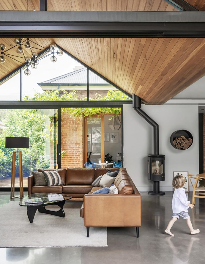 The pitched roof makes this room beautiful in the late-afternoon light. The facade is completely glazed and operable except for one panel, so the space becomes an open garden room. Custom leather sofa, Nordic Design. Nathan + Jac round cushion and Armadillo & Co 'Paragon' rug in Shadow, both Terrace Floors + Furnishings. Eadie Lifestyle linen cushions in various colours, Twopairs Homeware. Standing lamp, Freedom. Track lights, Brightgreen. Designer buy: Noguchi coffee table in Walnut, $5265, Living Edge.