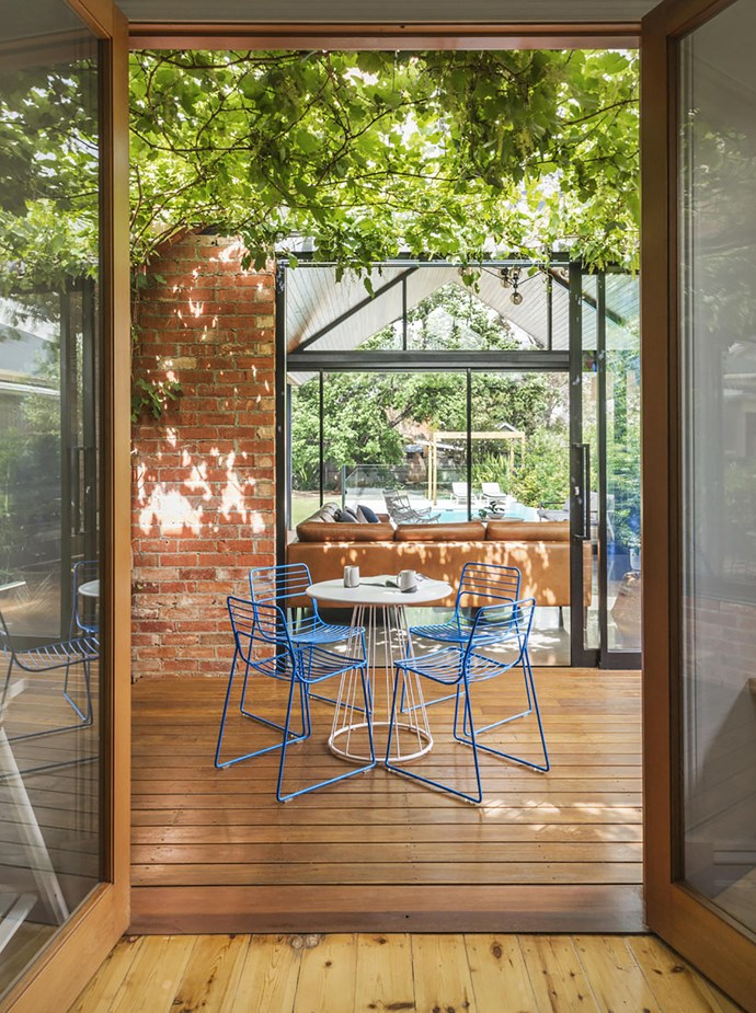 """This small open area with blackbutt decking sits between the new addition and rear of the original house. """"I can see all the way from my office to the yard, which is handy when the children area playing,"""" says Sally. Metal table and chairs from previous house."""