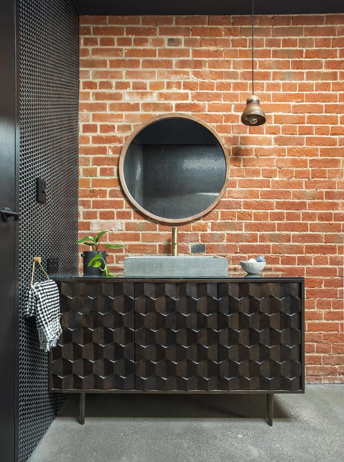 The home's exposed brick walls are original. Glazed penny-round tiles, Academy Tiles. Joinery designed by Sally Wilson and made by ABJ Kitchens. Concrete basin, Wood Melbourne. Walnut mirror, sourced through a contact. Hand towel, Eccola. Satelight 'Flare' pendant light, Brightgreen.