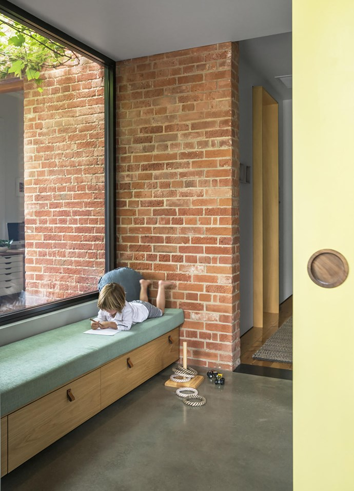 """This is what Sally and Mark call the transitional area between the old and new parts of the house. """"The passage contracts and compresses your sense of height before it opens into the living area,"""" Sally explains. The custom day bed is one of Huxley's favourite places. Quoits game, Flourish Gift and Home."""