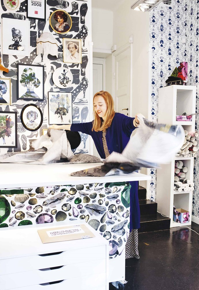 """**Work studio** The base of Lisa's bench is covered in 'Disco', one of her jewel-like fabric patterns. Her shoe-inspired 'Svärmor' wallpaper is masked by prints and photos, including one of her grandmother Ann-Marie. Lisa's outfit by [Carin Rodebjer](https://www.rodebjer.com/wo/home