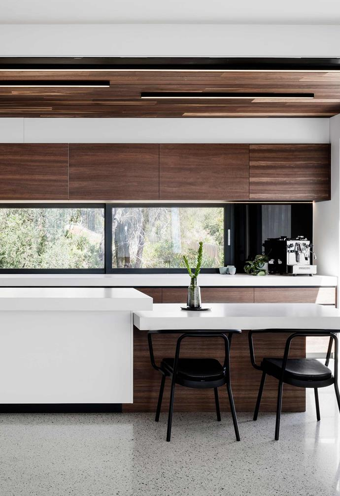 "**Function meets form** In this  [ultra-modern coastal home](https://www.homestolove.com.au/modern-coastal-house-19462|target=""_blank"") the kitchen island features a designated seating zone which serves both a functional and aesthetic purpose. Spotted gum lines the cabinetry and ceiling, providing juxtaposition to glossy white benchtops and the polished concrete floor. *Design: [Megowan Architectural](http://m-a.com.au/
