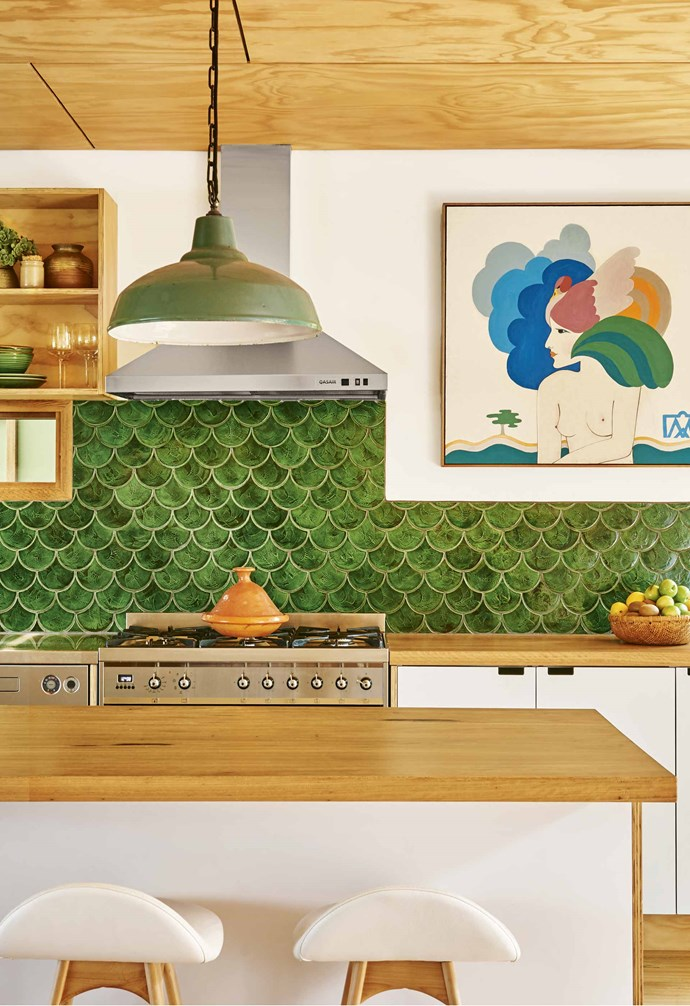 "**Be bold** The dramatic green fish scale tiles in this [coastal home](https://www.homestolove.com.au/second-life-a-coastal-home-filled-with-vintage-finds-18573|target=""_blank"") makes a vibrant statement. Timber benchtops mirro the timber-lined ceiling and flooring, and white walls and white cabinetry break up the palette. *Styling: Emma O'Meara 