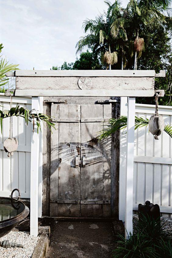 """An unassuming gate at Heidi Daburger's [eastern-inspired Byron Bay property](https://www.homestolove.com.au/eastern-promise-an-exotic-light-filled-bangalow-cottage-12338
