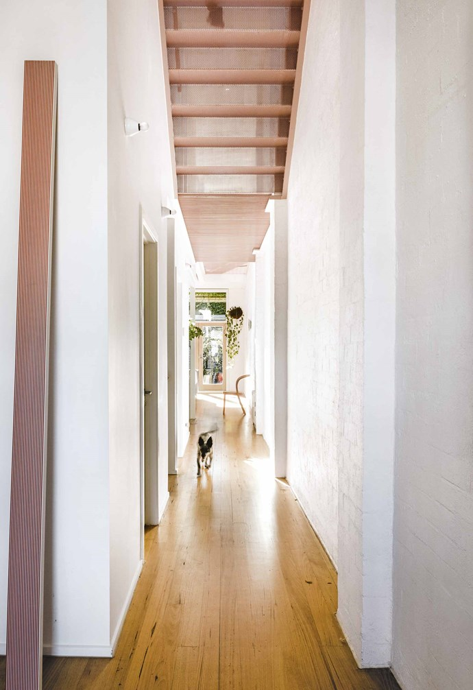 """The most striking element is the candy-pink metal staircase and walkway, where the original structure has been matched with perforated powder-coated steel treads. The play of light, movement and pattern is a beautiful reward. """"It creates a real sense of interest in the space and draws your eye up,"""" says Sarah.<br><br>**Hallway** """"The light throughout the day creates this beautiful glow of warm patterns and shadows,"""" says Sarah. At the top of their wishlist was a rework of the walkway: """"It was very stark and unfriendly with a metal grill and quite big gaps, almost like what you'd see in a factory."""""""