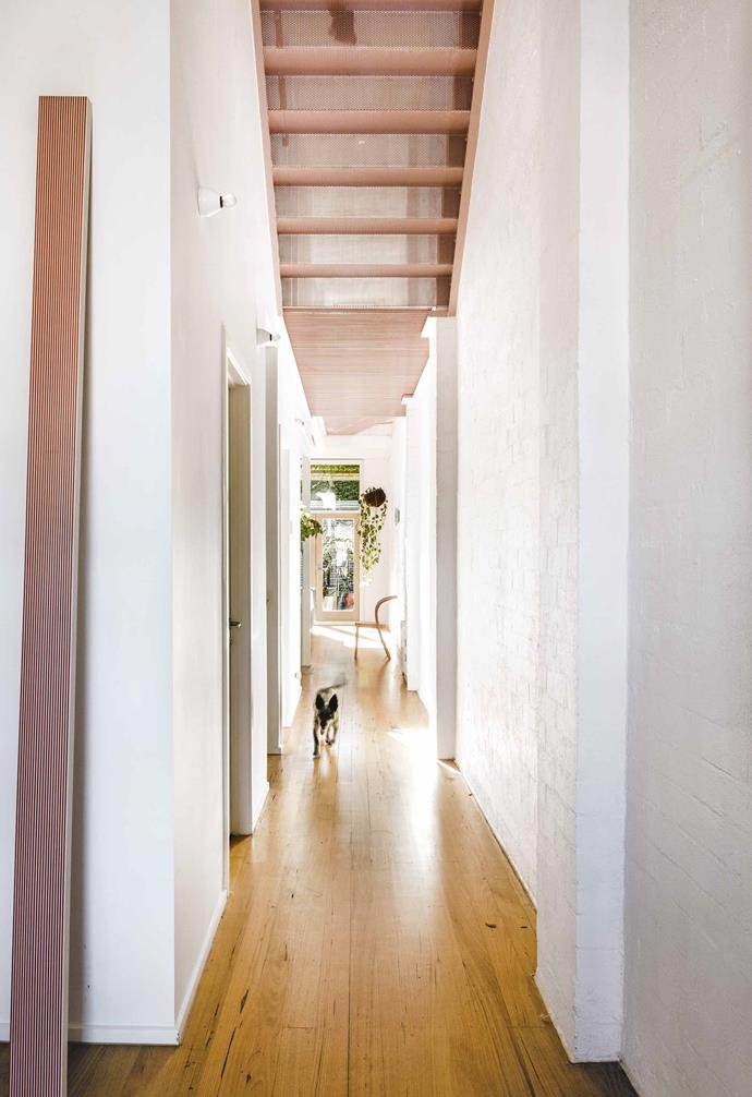 "The most striking element is the candy-pink metal staircase and walkway, where the original structure has been matched with perforated powder-coated steel treads. The play of light, movement and pattern is a beautiful reward. ""It creates a real sense of interest in the space and draws your eye up,"" says Sarah.<br><br>**Hallway** ""The light throughout the day creates this beautiful glow of warm patterns and shadows,"" says Sarah. At the top of their wishlist was a rework of the walkway: ""It was very stark and unfriendly with a metal grill and quite big gaps, almost like what you'd see in a factory."""