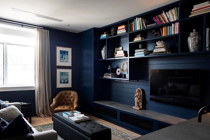 **After:** The lower level features a guest-bedroom-come-media-room, an intimate and cosy space that, with its Resene Shadowy Blue walls and dark artwork, contrasts with the rest of the house.