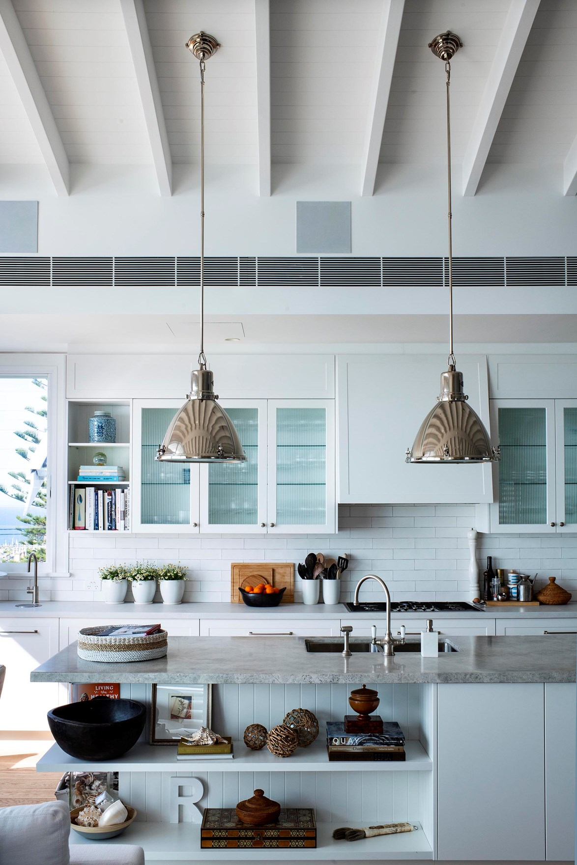 "Ralph Lauren lights hang in the [Hamptons-style kitchen](https://www.homestolove.com.au/deborah-huttons-hamptons-style-kitchen-renovation-19109|target=""_blank"")."