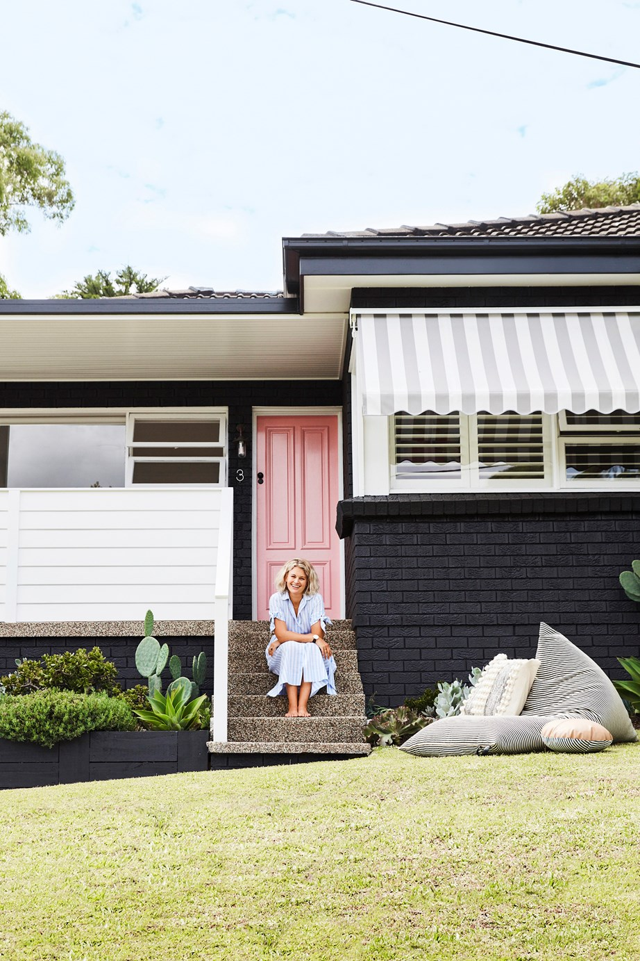 "This old [red brick home](https://www.homestolove.com.au/red-brick-house-renovation-australia-19757|target=""_blank"") has been completely refreshed with a bright pink front door, retractable awnings, timber panelling on the balcony surround and fresh coat of Taubmans 'Casino' on every surface."