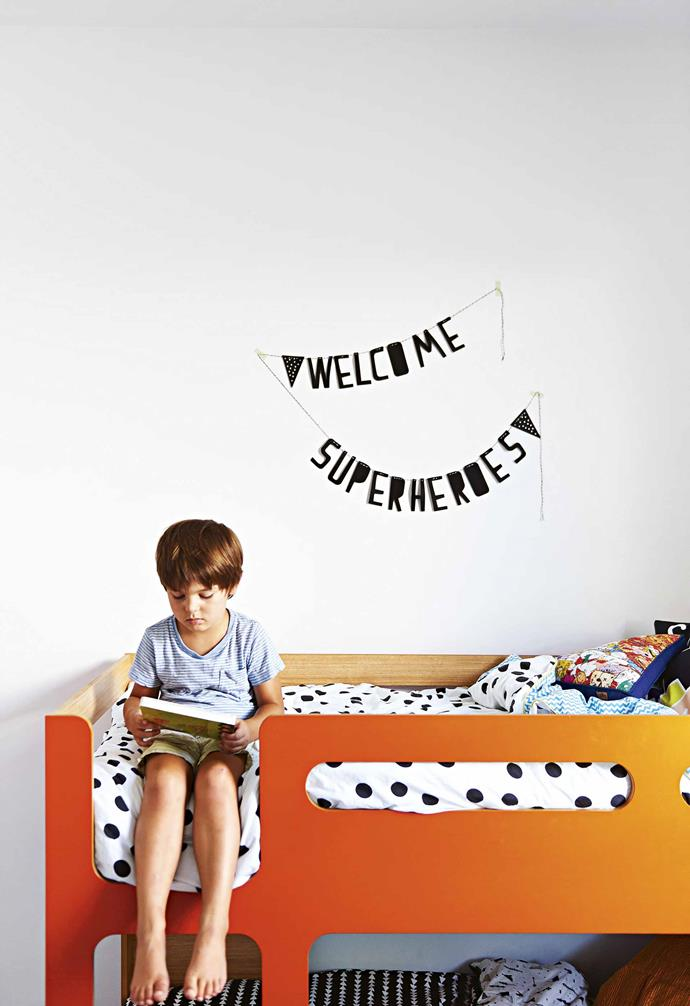"There are also plenty of [child-friendly choices](https://www.homestolove.com.au/shannon-vos-how-to-design-your-home-to-be-kid-friendly-14949|target=""_blank""), including a commercial plastic carpet in the playroom and one of the couple's favourite features, a huge timber-framed glass door that separates the playroom from the rest of the living area. Wherever you are in the downstairs area though, you can see the kids whether they're watching TV in the living area or playing in the yard.<br><br>**Boys' room** Teddy sits at the top bunk of this bed from Domayne."