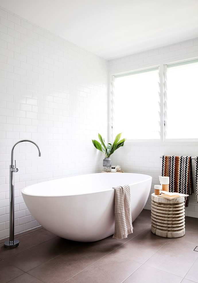 Rachel created the white bathroom using Tiles By Kate subway tiles with Caesarstone benchtops and a freestanding Luna 1680 stone bath from Bathroom Warehouse.