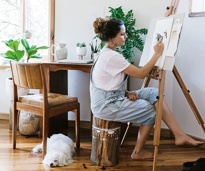 Artist Brigitte May painting at an easel with dog by her side