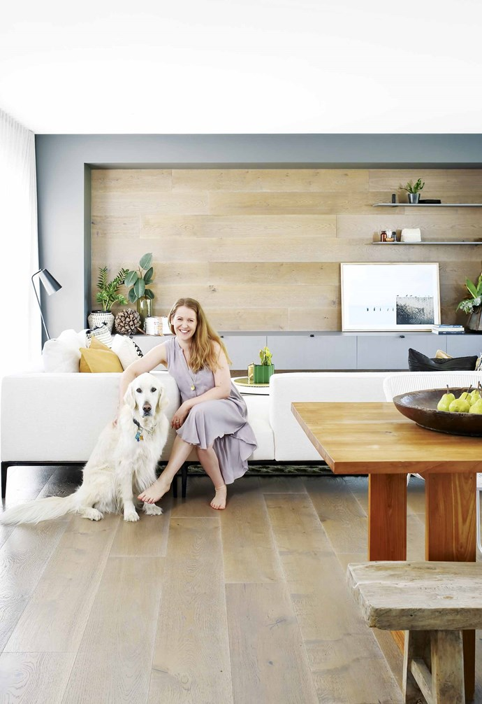 """**Living area** Homeowner Megan Fenner with her dog Henry. Interior designer Luisa Klinge of Arki Haus came up with a series of clever timber wall panels for the TV cabinetry, to hide all the cords and cables. Artwork by [Alanna Jayne McTiernan + Co](http://www.alannajaynemctiernan.com/