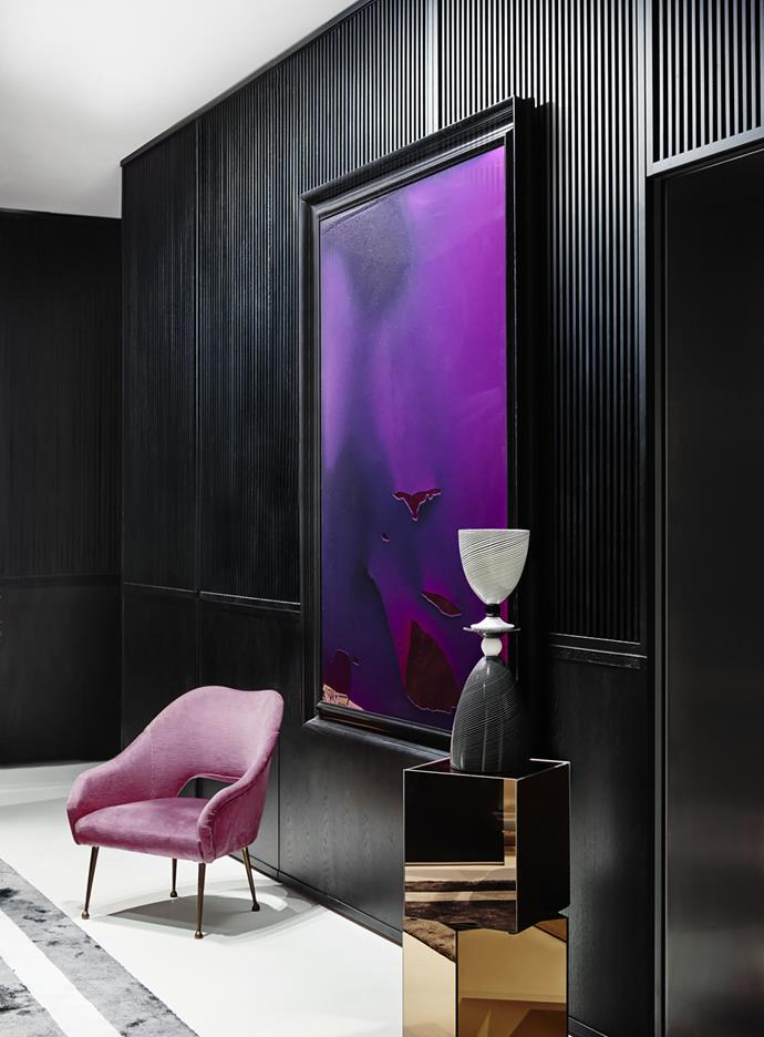 In the foyer, ribbed wall panelling in European oak with hand-rubbed black japan finish. Vintage chair from Smith Street Bazaar and glass sculpture by Mark Douglass. Artwork, Taking her by the hand, being mean is a pressing necessity he said by Dale Frank, from Neon Parc.