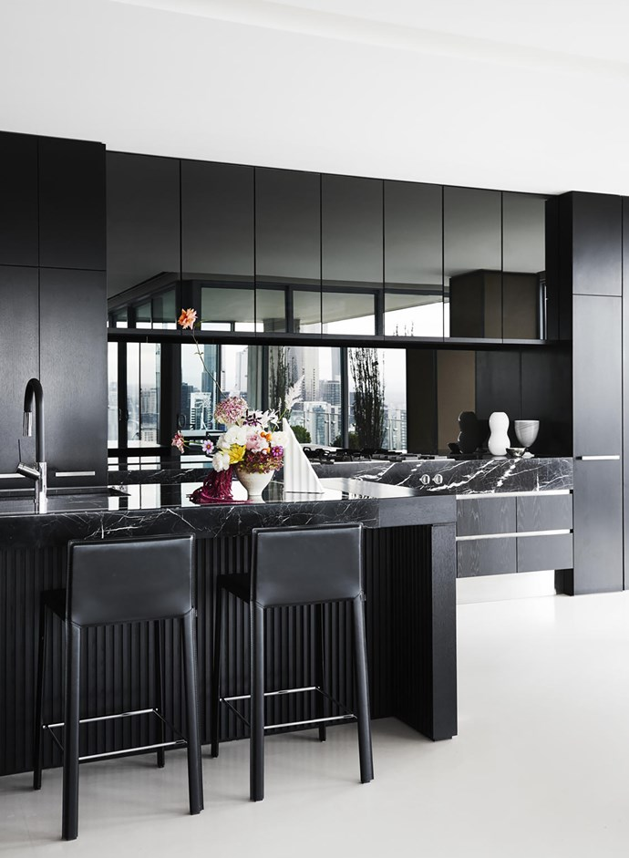 European oak cupboards with black japan finish and silver mirror splashback. Nero Marquina marble benchtops. Stools from Fanuli. Sculpture by Sean Meilak.