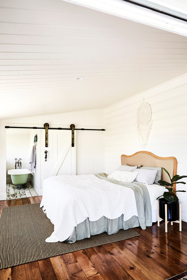 The owners of this old Queenslander home, decided to give their master bedroom a hotel-feel by adding an ensuite concealed behind a sliding barn door.