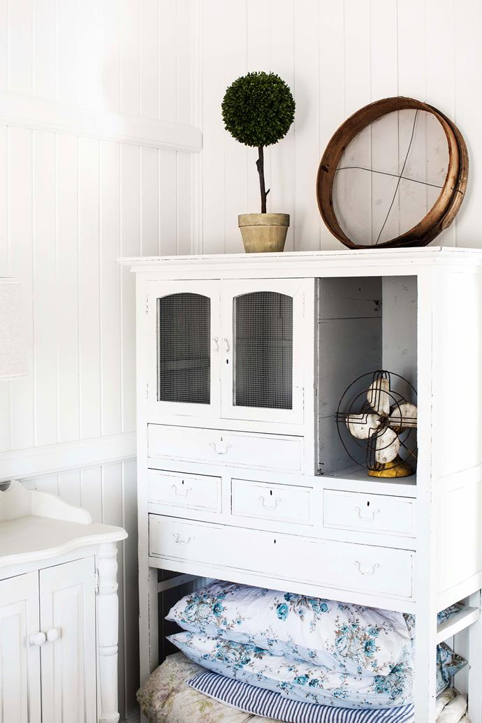 An old medicine cabinet has been re purposed as a storage unit in the bedroom.