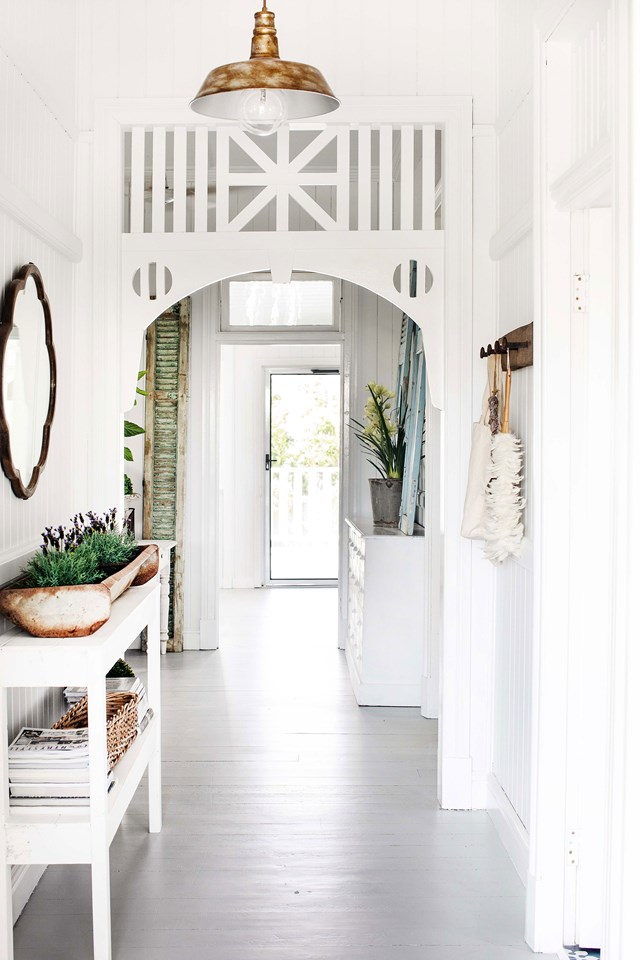 "Featuring fretwork and high ceilings, the entrance to this [renovated Queenslander](https://www.homestolove.com.au/queenslander-white-interior-colour-scheme-19786|target=""_blank"") is a taste of the charming, light-filled interiors that lies beyond."