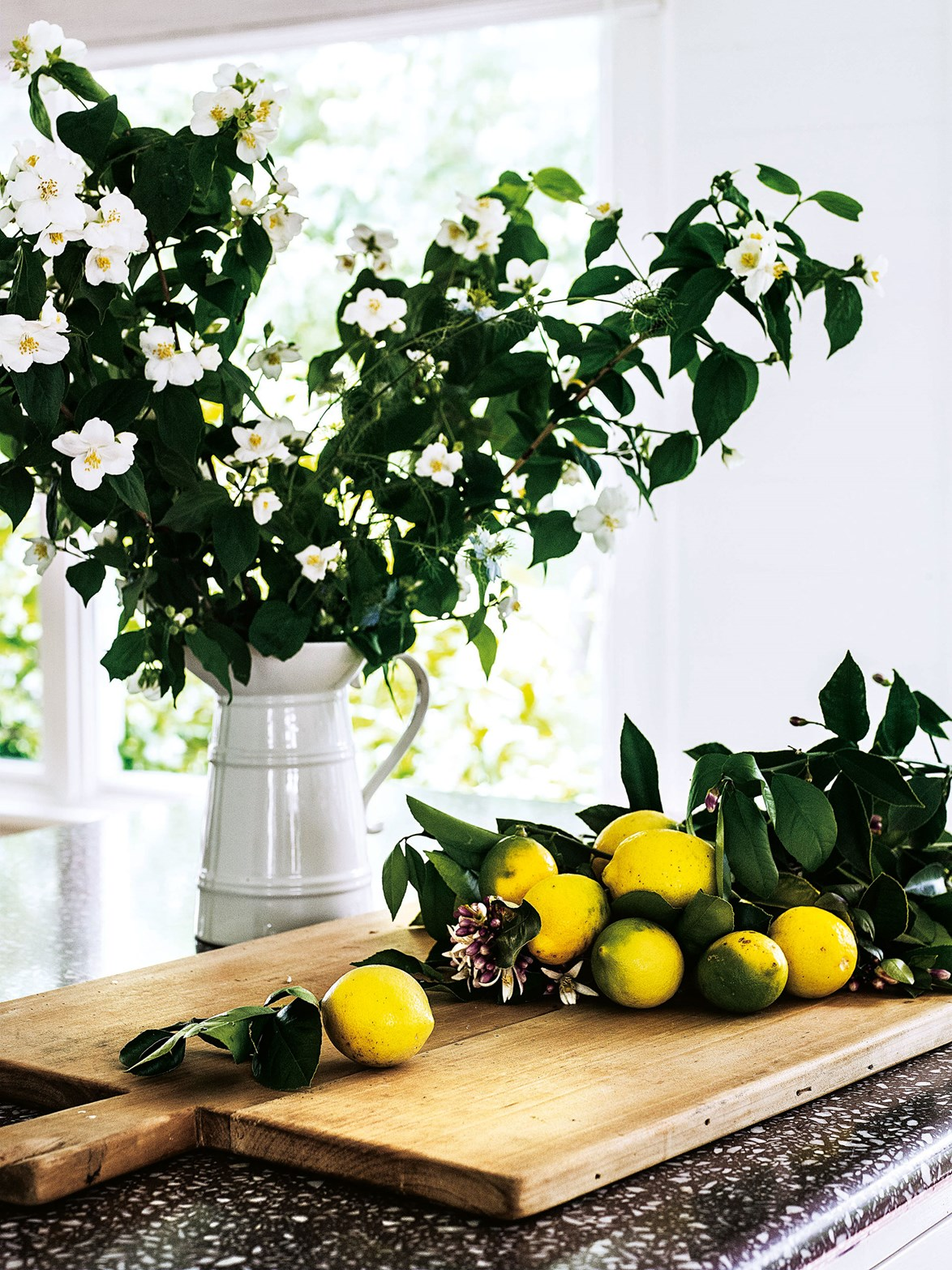 Flowers and fresh fruit en masse is one of the easiest ways to freshen up your kitchen. If you're blessed with a large kitchen bench, opt for tall stems that make a statement.