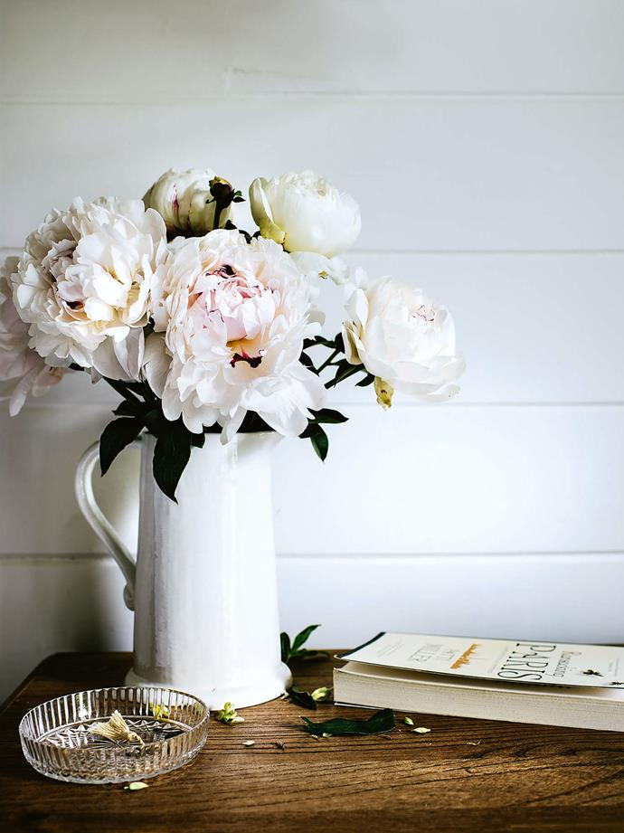 "[Fresh-picked peonies](https://www.homestolove.com.au/how-to-grow-peonies-10659|target=""_blank"") in a Country Style 'Tilba' jug in the master bedroom."