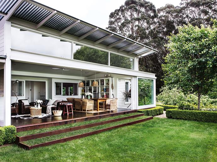 "A [sliding glass door](https://www.homestolove.com.au/open-plan-window-ideas-19465|target=""_blank"") spans the width of the glass extension, rolling right back to open the house to the garden and views beyond. ""When we built this, it killed every other room in the house!"" Michael says. To extend the green space at the back of the house, the couple grassed over the steps."