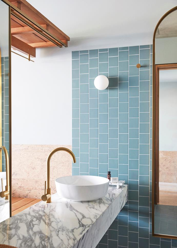 A private bathroom is decked out in swimming pool-blue tiles, marble and brushed brass.