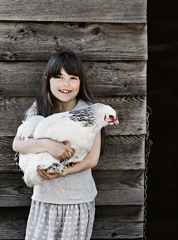 Lucy hugs a Light Sussex chicken.
