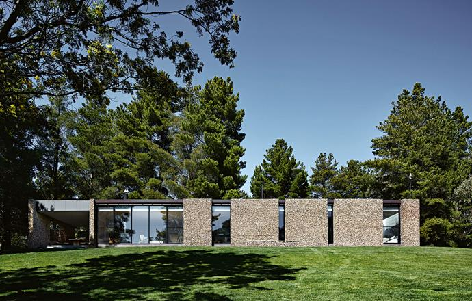 """The [exterior facade](https://www.homestolove.com.au/how-to-transform-your-homes-facade-3925 target=""""_blank"""") is made of cement sheet with the gabions forming a cosmetic face at the front. Gabions also create thermal mass and have a secondary insulating function. The Quinns built the gambions themselves, filling the mesh cages, which were joined together with metal clips, with small rocks. """"It was all done as a labour of love over time and happily, willing helpers were available,"""" Jeannie says."""