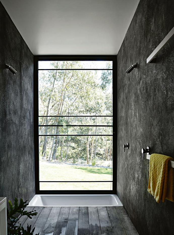 Everything in the compact second bathroom works to draw the eye towards the bush views beyond the window. A sunken tub makes the room feel larger.